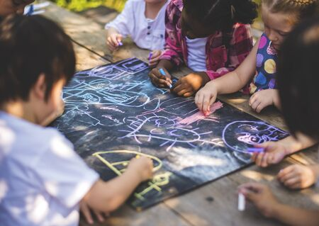 多様なグループが黒板の図面を一緒に子供たち