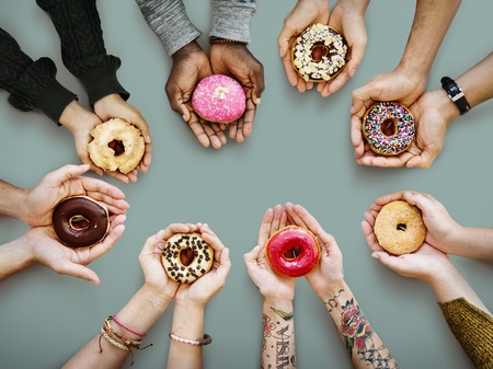 Hands holding donuts