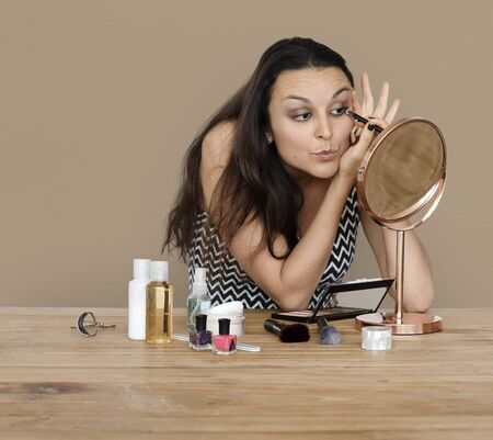 Woman making up her face with cosmetics