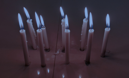 Candle on the table in the darkness