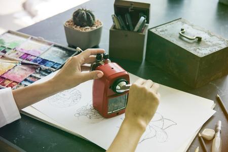 女性は黒いテーブルの上の鉛筆を削る 写真素材
