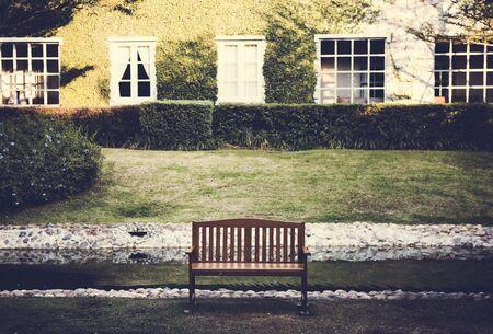 녹색 잔디 마당 앞에서 휴식을위한 벤치 스톡 콘텐츠