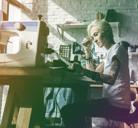 messy clothes: Fashion designer tattooed girl on her workspace
