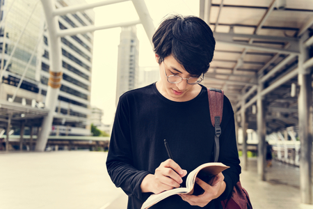 Asian man holding notebook and walking in the city