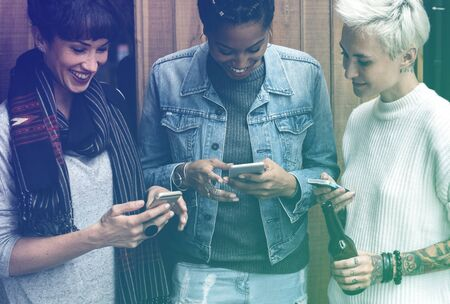 Group of girlfriends connected by mobile phone network