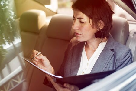 Businesswoman signing contract on backseat of the car Stock Photo