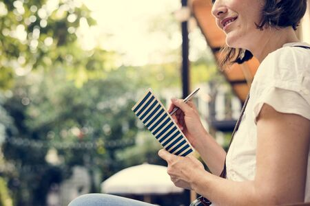 Adult Woman Sitting Hand Holding Notebook Thoughtful