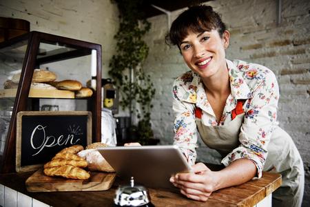 パン屋さんでタブレットを使用して大人の女性 写真素材