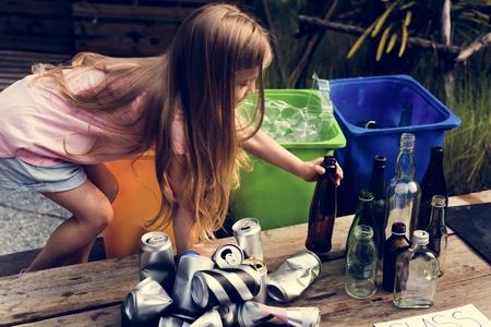 Het meisje is afzonderlijk afval om te recycleren Stockfoto