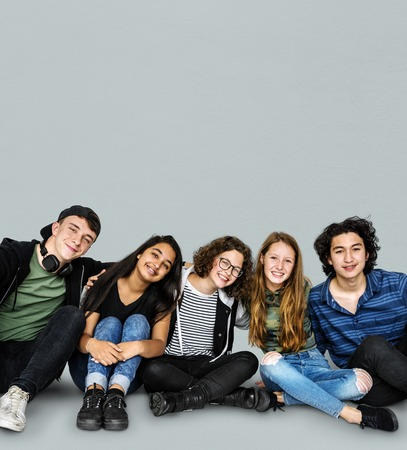 Group of young people sitting on floor Imagens