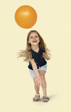 オレンジ色のボールを持つ白人少女