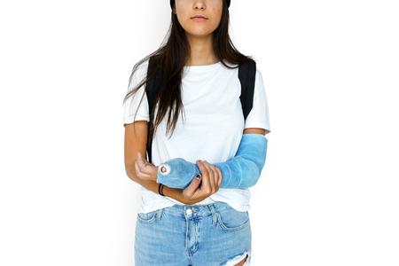 骨折した腕のスタジオ ポートレートと若い成人女性