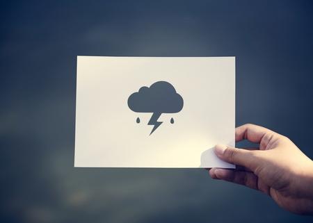 Menselijke hand die regenachtige wolk geperforeerde document ambacht in aard houdt Stockfoto