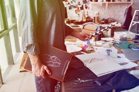 messy clothes: Fashion designer holding clipboard of dress pattern