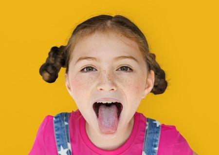 Felicità sorridente della bambina che attacca fuori il ritratto dello studio della lingua Archivio Fotografico - 80280464