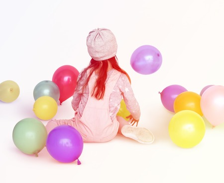 Young girl sitting and playing with balloons Reklamní fotografie