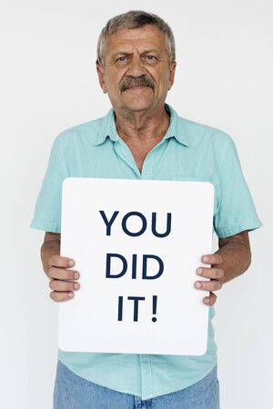 Senior adult man smiling and holding you did it banner