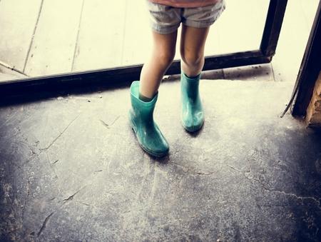 Kind trägt Stiefel, die hereinkommen Standard-Bild - 80370163