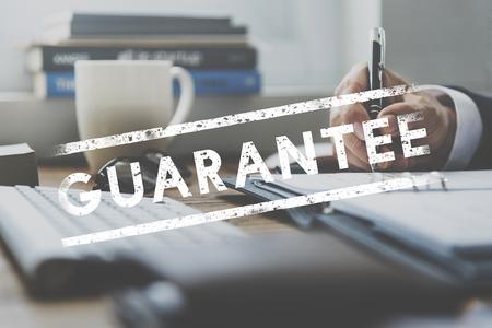 Geschäftsmann arbeitet am Tisch mit Garantie Wort Standard-Bild - 80341075