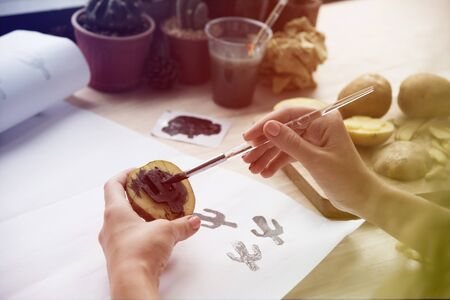 Woman painting potatoes on wooden desk Stock Photo