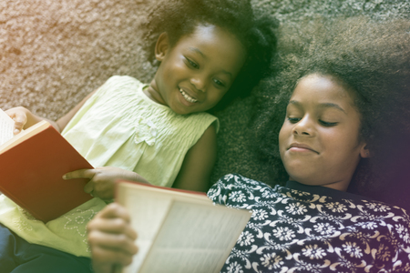 Little Girls Lay On The Floor Reading Book Sisterhood Stock Photo