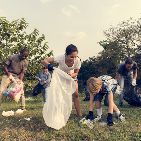 Diverse Group of People Picking Up Trash in The Park Volunteer Community Service