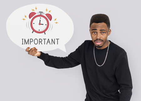 African man holding speech bubble alarm clock icon Stock Photo