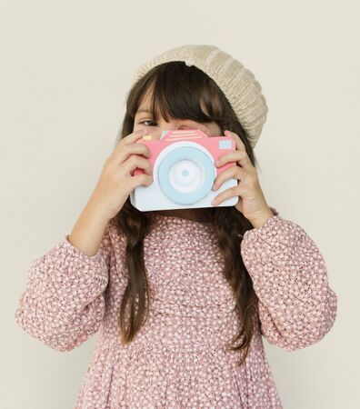 beanie: Little Girl Holding Papercraft Arts Camera Photogrphing Studio Portrait Stock Photo