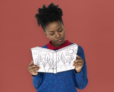 Una niña paga atención leyendo un libro Foto de archivo - 80376140