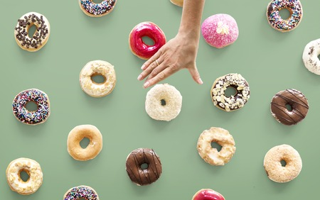 fattening: Hands selecting a variety of donut flavour
