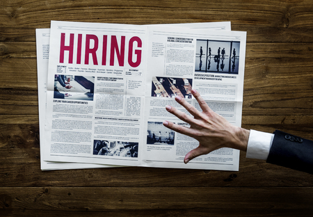 Hand Reach Out for Career Hiring Job Announcement on Newspaper