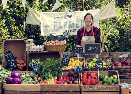 Greengrocer selling organic fresh agricultural product at farmer market Stok Fotoğraf