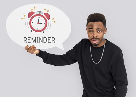 African man holding speech bubble alarm clock icon Stock Photo