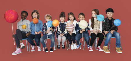 Diverse group of kids holding planets on sticks isolated background Stock Photo