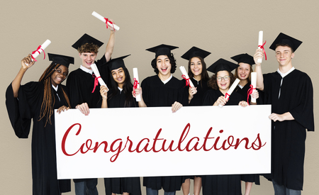 Diverse Students wearing Cap and Gown Showing Congratulations Sign Studio Portrait Stock Photo