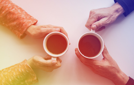 People hands holding coffee cup in aerial view