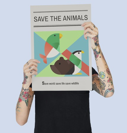 species living: Tattooed woman with save the animals banner Stock Photo