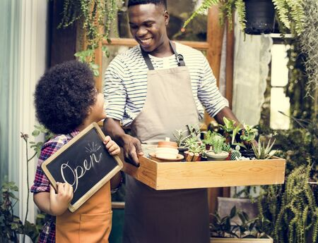 Man Carrying Plants Standing With Son Showing Open Sign Stock Photo