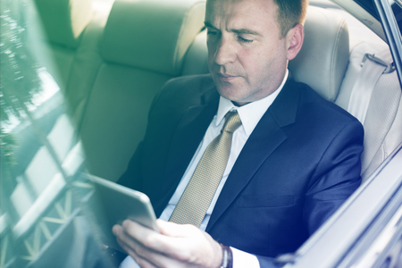 Businessman using digital tablet on backseat of the car Stock Photo