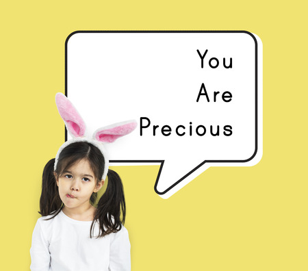 Portrait of young girl with bunny ears headband, You Are Precious text bubble overlay