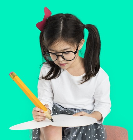 Studio portrait of a young girl wearing glasses drawing with a giant pencil