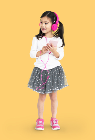Studio portrait of a young girl listening to music with pink headphones