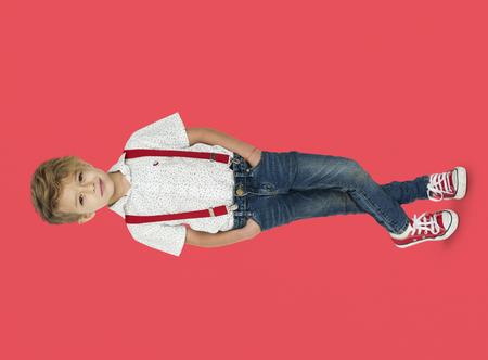 Un ragazzo caucasico che sta attraversando le gambe sfondo di studio ritratto Archivio Fotografico - 80732897