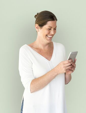 entertaining: Adult Woman Using Mobile Phone Cheerfully Stock Photo