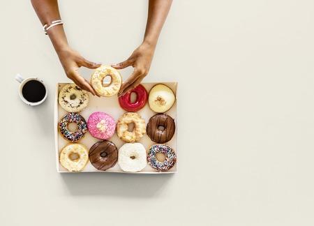 Hands holding sweeten donut dessert in aerial view 版權商用圖片