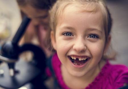 Caucasian girl is smiling with microscope behind