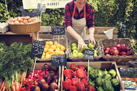 Greengrocer preparing organic fresh agricultural product at farmer market Archivio Fotografico