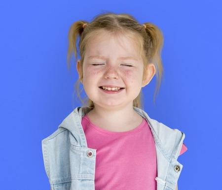 幸せ遊び心のあるツインテールの髪型を笑っている小さな女の子 写真素材