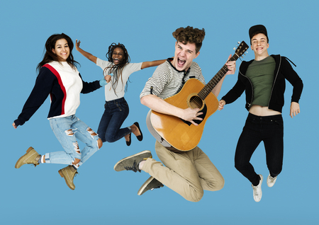 entertaining: Young Adult People Jumping with Guitar Studio Portrait
