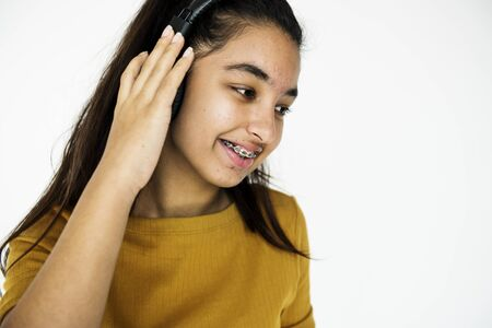 music background: Young adult girl smiling and listening music studio portrait